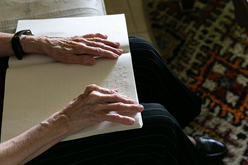 Cuban-American Adelina Maideski, a former gift store employee at Miami International Airport who attends St. Martha Parish in Miami Shores, reads braille Catholic materials at her residence.