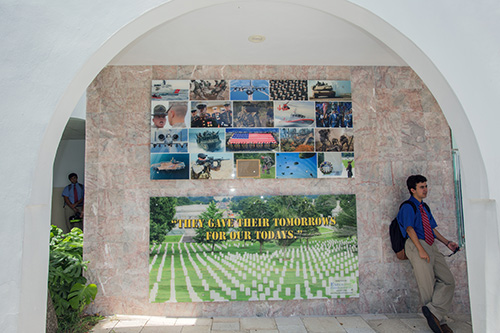 A Christopher Columbus student stands next to the military memorial wall at the Miami high school.