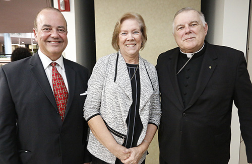 Joan Crown poses with incoming Respect Life Director Juan Guerra and Archbishop Thomas Wenski, during her retirement party at the Pastoral Center Oct. 4.