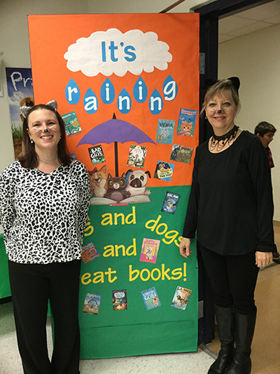 It's raining cats and dogs and great books: Dressed in kitty couture, St. Mark the Evangelist School teacher Danielle McConnel and media specialist Sandy Garcia pose by the door to the library during the Scholastic Book Fair, which later won the school first prize in the Scholastic Spring 2018 National Elementary School Contest.
