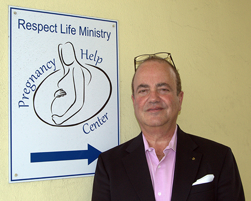 Juan Guerra poses at the entrance of the South Broward pregnancy help center. It's part of the archdiocesan Respect Life Office, where he's the new executive director.