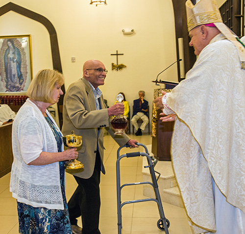 Founding parishioner Lou Huertas and Eileen Cahill, a parishioner since 1975, bring up the offertory to Archbishop Thomas Wenski.