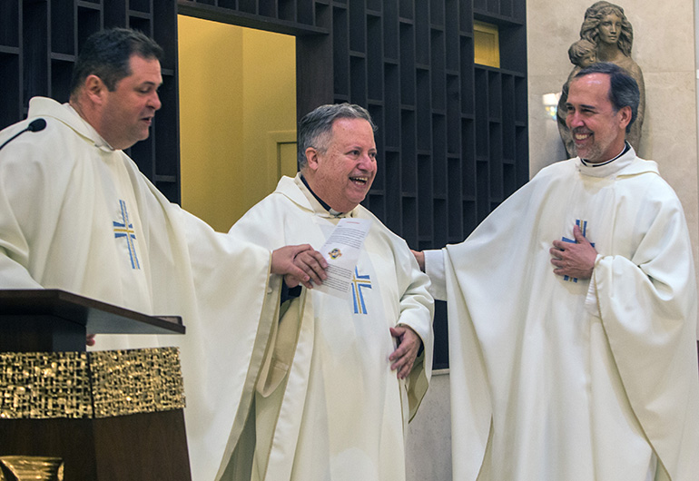 Current administrator Father Rolando Cabrera, left, and former pastors Father Juan Sosa and Father Alejandro Rodriguez Artola, share a laugh during St. Catherine of Siena Church's 50th anniversary Mass.
