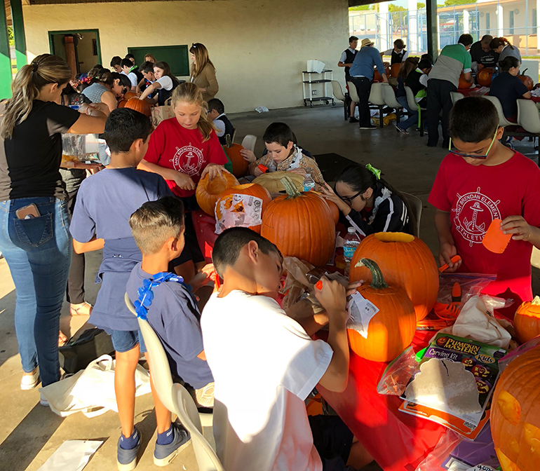 St. Brendan Elementary students work on their STREAM project, turning pumpkin guts into slime.