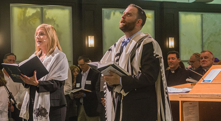 Cantorial soloist Jodi Rozental and Rabbi Jonathan Fisch, holding prayer books, lead the congregation in prayer as Father Richard Vigoa, archbishop's priest secretary, and Archbishop Thomas Wenski look on in the background.