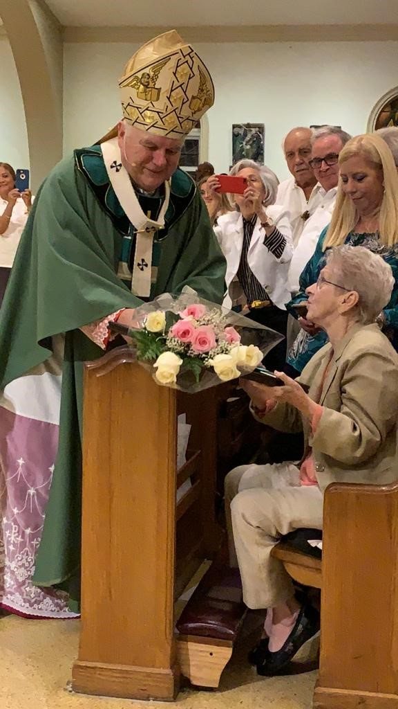 Archbishop Thomas Wenski presents a bouquet of flowers to Myrna Gallagher, who together with Father David Russell, then pastor of St. Louis in Pinecrest, started the Emmaus retreats in the archdiocese in 1978. The movement marked its 40th anniversary with a Mass Nov. 3 at St. Mary Cathedral.