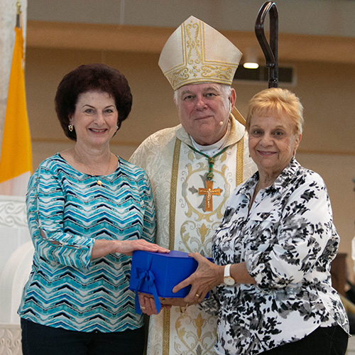 Camille Laurino, left, and Rosalie Constantino, pose with Archbishop Thomas Wenski after receiving this year's Esperanza Ginoris Award for excellence in a catechetical program. The annual Catechetical Day was held Nov. 3 at Archbishop McCarthy High School in Southwest Ranches.