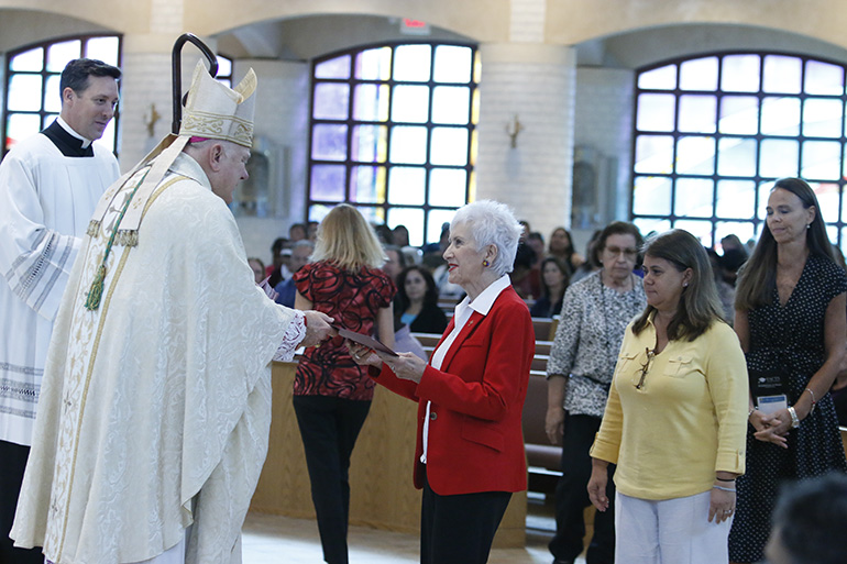 Catechists with more than 20 consecutive years of service, all as volunteers, receive their certificates of appreciation at the Mass that preceded the annual Catechetical Day held Nov. 3 at Archbishop McCarthy High School in Southwest Ranches.