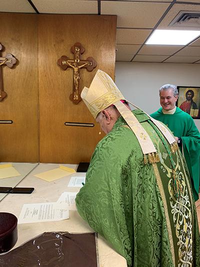 El Arzobispo Thomas Wenski firma los papeles que hacen oficial el nombramiento  del P. Lazarus Govin, a la derecha, como párroco de la iglesia St. Martha en Miami Shores.