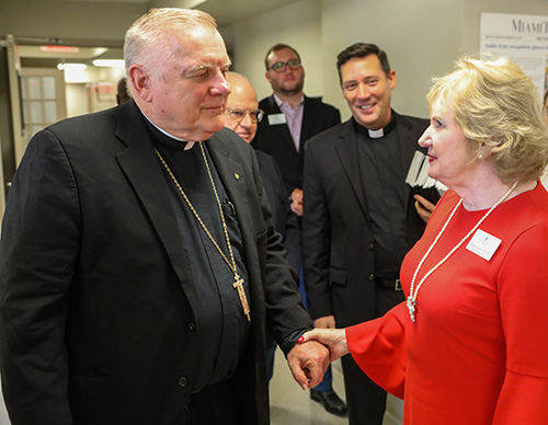 Archbishop Thomas Wenski speaks with Virginia A. Jacko, president and chief executive officer of the Miami Lighthouse for the Blind & Visually Impaired, during a visit to the facility Nov. 8, 2018.