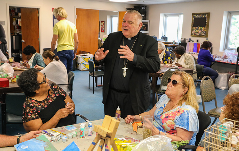 Archbishop Thomas Wenski speaks with participants in the Miami Lighthouse for the Blind's Senior Group Health and Activities Program during a visit to the facility Nov. 8.