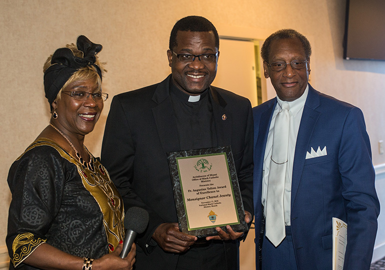 Katrenia Reeves Jackman, director of the archdiocesan Office of Black Catholic Ministry, poses with Msgr. Chanel Jeanty, the ministry's chaplain, who was honored with a special award, the Father Augustus Tolton award of excellence. At right is Donald Edwards, associate superintendent of schools for the archdiocese.