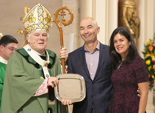 Juan and Natalie Bauta of St. Louis Parish in Pinecrest receive this year's One in Faith award from Archbishop Thomas Wenski. The award highlights their commitment to