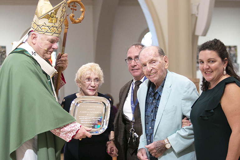 Katherine and Joseph Allen of St. John the Baptist Parish in Fort Lauderdale, accompanied by their son, Daniel, rear, and daughter Mary Delia Allen, far right, receive this year's One in Charity award from Archbishop Thomas Wenski. The award highlights their constant support to the Archbishop's Charities and Development Drive.