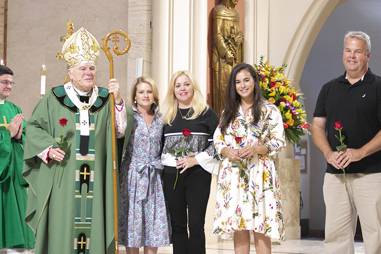 New members of the Archbishop Coleman Carroll Legacy Society pose with Archbishop Thomas Wenski during the annual ThanksforGiving Mass. The roses recall the words of St. Therese of the Little Flower, who said she wanted to spend her eternity in heaven doing good works on earth.
