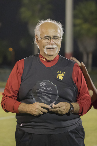 Retiring Pace football coach Joe Zaccheo receives a commemorative plaque Nov. 2, when the Pace Spartans and the Belen Wolverines had their annual match-up at the Knights of Columbus Turkey Bowl.