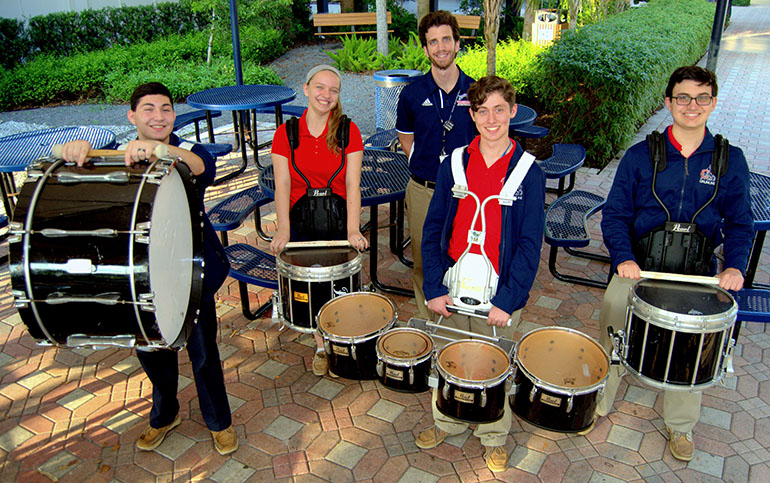 Presidents of the Chaminade-Madonna High School drumline, are, from left, Justin DiFrancesco, Taylor Despars, Fabian Carrillo and John Mendez. Behind them is their instructor, Carlo Ricchi. The drumline has been invited to perform at Christmas Near the Beach, a community holiday celebration.