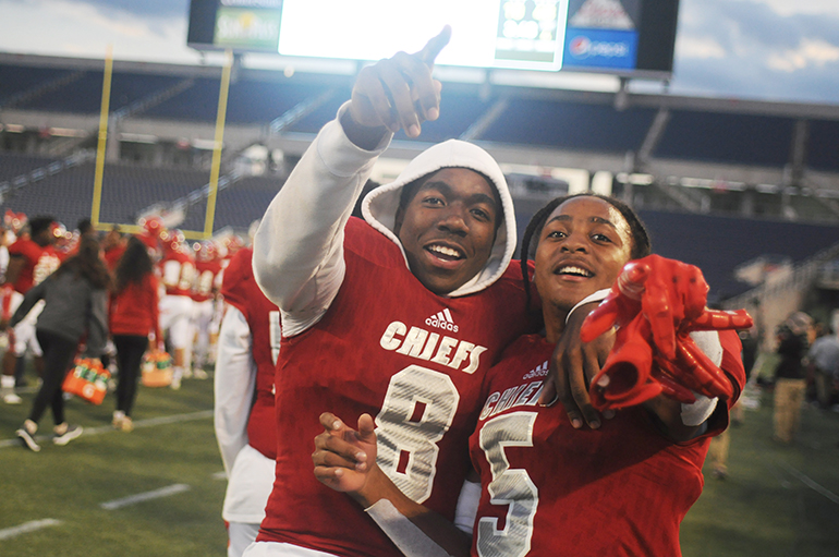 Cardinal Gibbons teammates Sidney Porter, left, and Vincent Davis celebrate their state championship victory over North Marion.