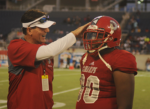 Cardinal Gibbons assistant football coach Lukas Kammatas and defensive lineman Terry Mareus celebrate the Chiefs' victory.