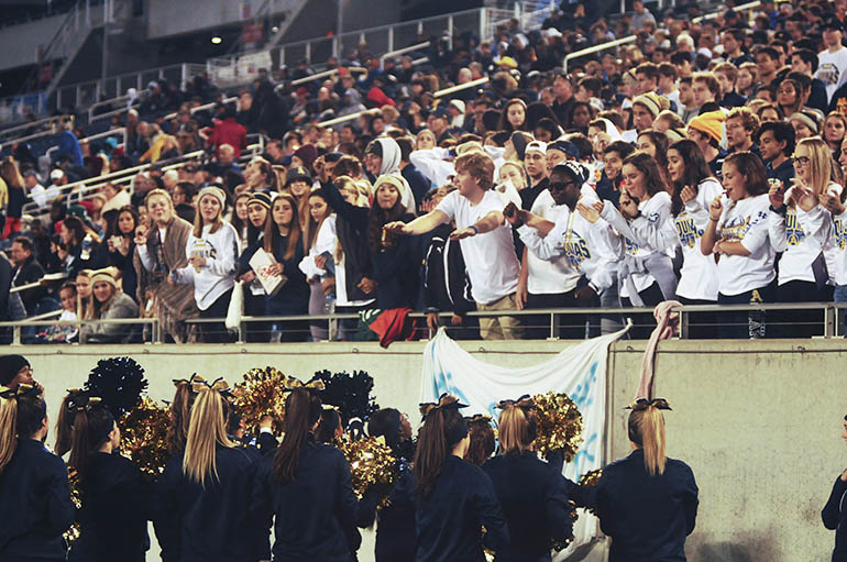 St. Thomas Aquinas cheerleaders and the student section exchange cheers during the first half Friday.