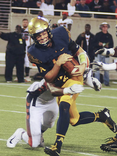 St. Thomas Aquinas quarterback Curt Casteel tries to break a tackle by Lakeland's Lloyd Summerall during the second half Friday.