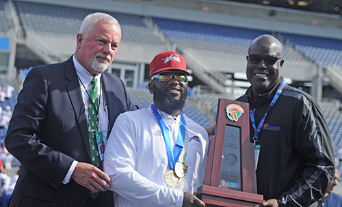 Chaminade-Madonna coach Dameon Jones, center, accepts the state-championship trophy from FHSAA Executive Director George Tomyn, left, and FHSAA board member Herschel Lyons.