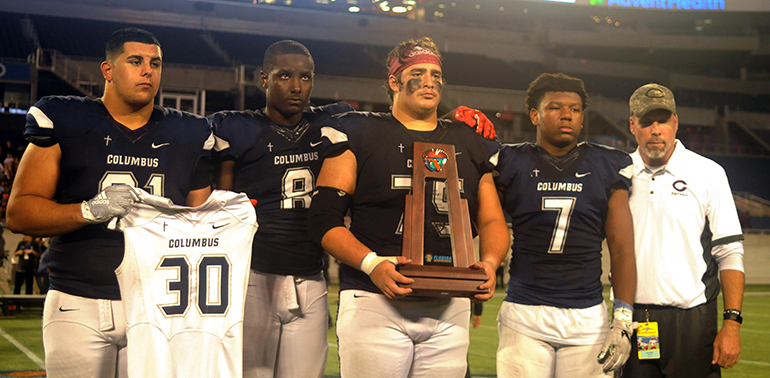 Columbus captains (from left) Dylan Perez, Jeramy Passmore, Luis Cristobal and Jordan Griffin pose with coach Chris Merritt with the runner-up trophy. Perez is holding up the No. 30 of defensive back Ari Arteaga, who died July 28 in a car wreck.