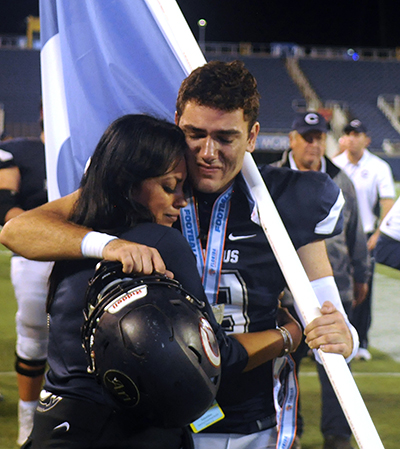 Columbus quarterback Armando Parra is consoled by Columbus fan Minnie Catala, president of the Columbus High Quarterback Club, after the Explorers' 37-35 loss to Mandarin in the FHSAA 8A football final Dec. 8.