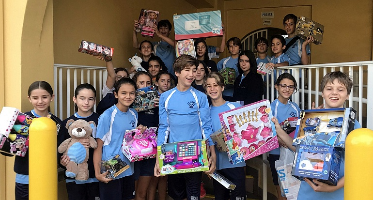 St. Agnes Academy students show some of the 1,000 toys the school collected for the Centro Mater Child Care Center in downtown Miami.