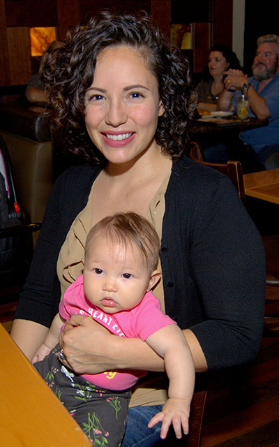 Raquel Acosta holds Noella, her 5-month-old daughter, during the inaugural dinner of Marriage Uncorked.