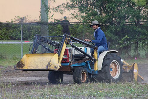 Happy farmer Moses Kashem rides a tractor as he prepares the Marian Center's land for more urban farming.