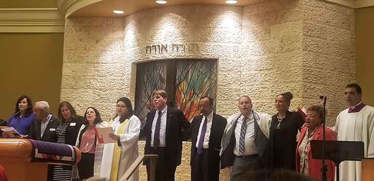 Leaders of all the faith communities represented at the annual Unity Service conclude the evening by singing God Bless America.