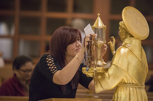 Eysac Aquino, parishioner at St. Mark Church in Southwest Ranches, prays in front of a relic of St. Anthony of Padua that was venerated at the church Dec. 3. Two relics from the basilica in Padua, Italy, traveled through South Florida churches Nov. 30-Dec. 9.