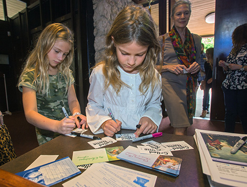 Charlotte Rosalski, 7, and Emilia Adams, 7, write their names on name tags before Mass Dec. 9 as part of St. Hugh's participation in the archdiocese-wide Welcome Weekend.
