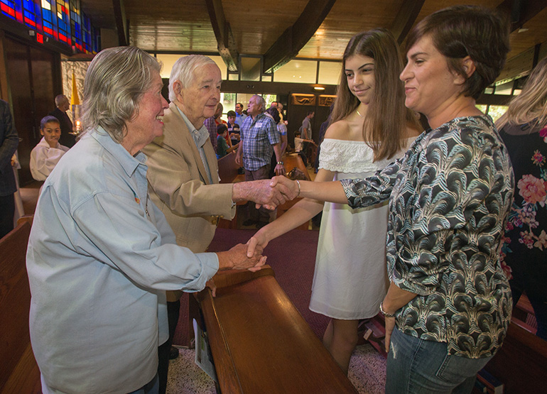 Kitty and Jim Harnett greet Anna Gatcliffe, 13, and Stacy Gatcliffe at the beginning of Mass Dec. 9 as part of St. Hugh's participation in Welcome Weekend in the Archdiocese of Miami.