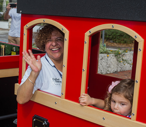 Cristina Fundora, St. Hugh Church's pastoral coordinator, waves from a window of the Mercy Train that offered rides around St. Hugh Church on Welcome Weekend.