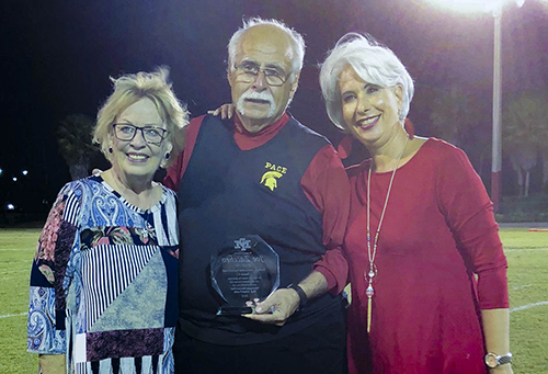 Msgr. Pace High School football coach Joe Zaccheo is pictured here with wife, Carol, left, and Pace principal Ana Garcia, after being recognized at the annual Turkey Bowl between Belen and Pace in November 2018.
