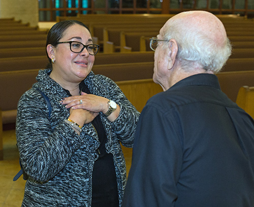 Parent Lesley Gray talks to Deacon John Lorenzo at the conclusion of one of the mandatory meetings for parents of religious education students.