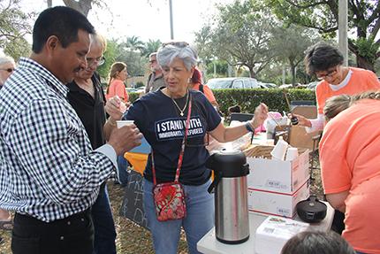 Un inmigrante hondureño, que llegó recientemente de su país, toma café mientras espera su hora de entrada a su cita de inmigración. A la derecha, Silvia Muñoz del Instituto Pedro Arrupe de Miami.