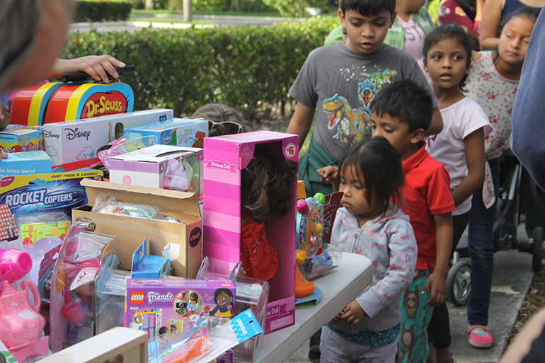 Children who accompany their parents to immigration appointments stand in line to receive toys for the feast of Three Kings. The toy distribution was organized by a group that calls itself the Círculo de Protección (Circle of Protection), which is made up of a number of community and social advocacy organizations. The volunteers meet every Wednesday in front of the ICE office in Miramar to hand out water, coffee and pastries to those waiting for their appointments.