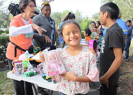 La niña guatemalteca Maili López, de 9 años, muestra el juguete que recibió por el Día de los Reyes Magos frente a las oficinas del ICE en Miramar, a donde acompañó a sus padres a su cita de inmigración, el 9 de enero.