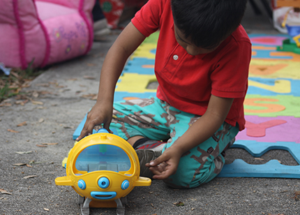 A boy plays with the toy he received while waiting with his parents outside the ICE office in Miramar.