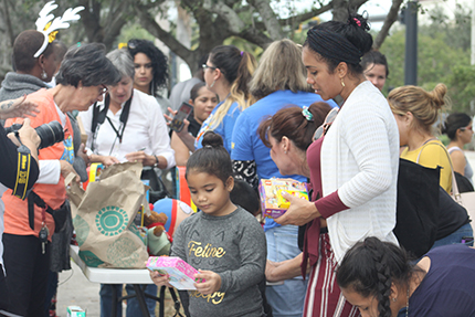 Luci Chemay and her mother, Luciela Manzano, look over the toy they received for the feast of Three Kings while waiting outside the ICE office in Miramar for their immigration appointment, Jan. 9.