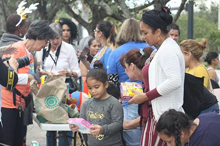 La niña Luci Chemay y su mamá Luciela Manzano, observan un juguete que escogieron por el Día de los Reyes Magos, frente a la oficina de ICE, en Miramar.