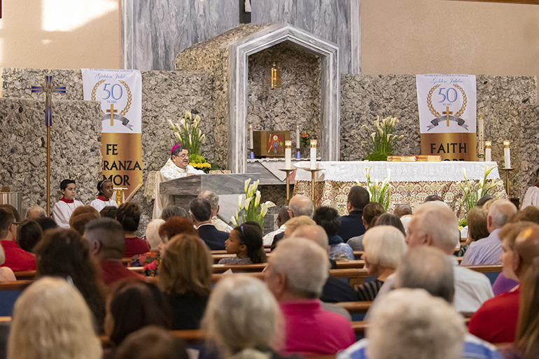 Auxiliary Bishop Enrique Delgado gives the homily during  the Mass marking the start of a year-long celebration of St. Henry Church's golden jubilee.