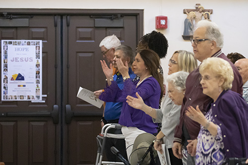 Parishioners pray during the Mass marking the start of a year-long celebration of St. Henry Church's golden jubilee.