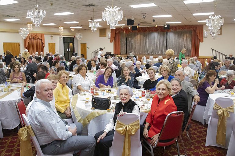 Parishioners gather for a reception after the Mass marking the start of a year-long celebration of St. Henry Church's golden jubilee. In the center table are members of the parish's Venezuelan group.