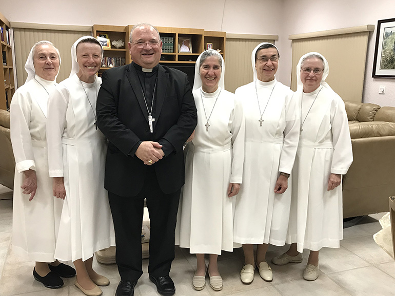 Auxiliary Bishop Peter Baldacchino is pictured here with the Sisters of St. Joseph Benedict Cottolengo who staff the Marian Center in Miami Gardens and the Hope Outreach Center in Davie. He joined them for Mass and dinner on the occasion of their annual renewal of their vows, this year on the feast of the baptism of the Lord.
