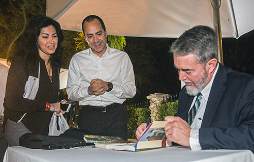 Vedro and Fabiola Torres watch as Scott Hahn signs a copy of his book,