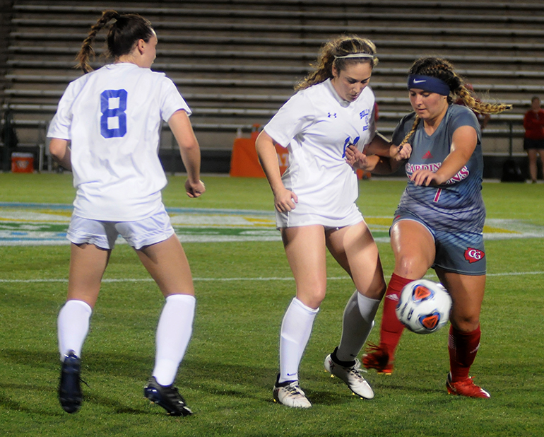 Cardinal Gibbons midfielder Brandi Orlando, right, duels Bolles midfielders Amelia Emas, center, and Aubrey Ramey during the first half Wednesday, Feb. 20, 2019. Bolles defeated Cardinal Gibbons 5-1 at Spec Martin Stadium in DeLand. It was Cardinal Gibbons' first state final since 2009.